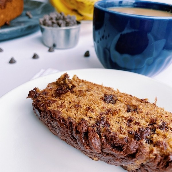 Slice of chocolate chip banana bread with coffee