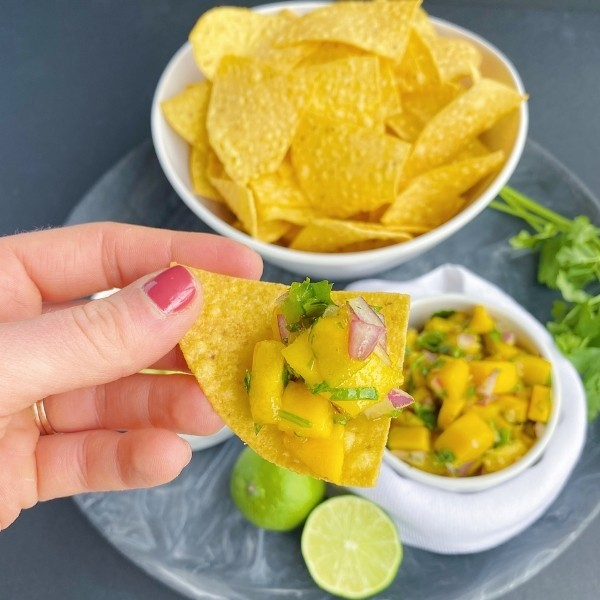 scooping up mango salsa with a tortilla chip