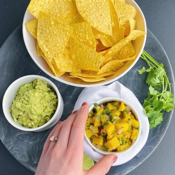 reaching for bowl of mango salsa